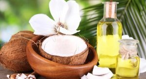 Coconuts and coconut oil on wooden table, on nature background